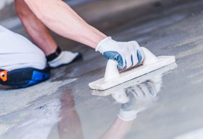 Man sanding floor on his knees